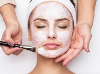 Woman receiving facial mask at beauty salon