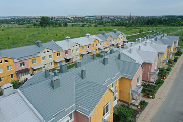 Aerial view of the townhouse and its long gray metal roof tile in Russia