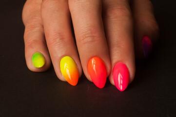 Obraz Kolorowe paznokcie przedstawione z bardzo bliska, na ciemnym tle - fototapety do salonu