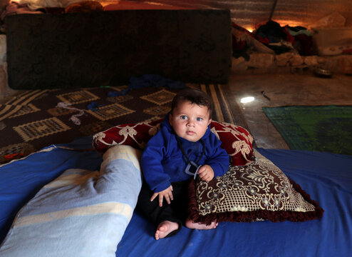 Displaced baby from south Idlib countryside, poses for a picture in a tent at Atmeh camp