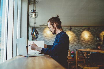 Side view of serious skilled male student studying information for knowledge textbook for put into chapter of course work, millennial man analyzing data from laptop comture and paper notepad Wall mural