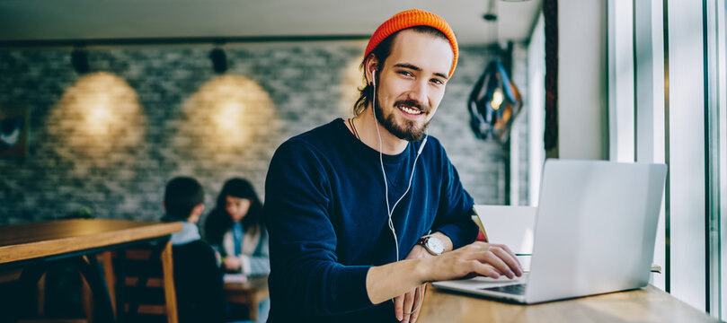 Portrait of happy smiling hipster guy enjoying time for favourite music playlist during e learning in cafeteria, positive male teenager in headphones rest indoors sitting at table with laptop device