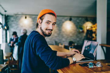 Skilled male it developer looking at camera coding on modern laptop computer working on freelance in cafe interior, portrait of cheerful hipster guy using netbook for e learning satisfied with course.