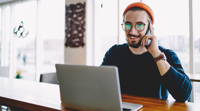 Portrait of cheerful hipster guy talking with friend about time of meeting in coworking space for e learning on laptop computer, happy man connected to public internet for calling via cellphone