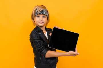 Stylish young boy in black jacket and white t-shirt serfing internet with his tablet