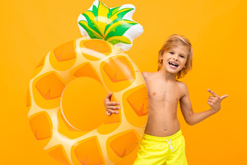 pretty European blond boy in yellow swimming trunks with swimming circle pineapple on an orange background