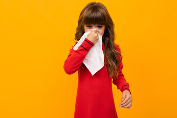Beautiful little girl in dress plays with glasses isolated on yellow and orange background