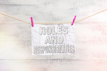Handwriting text writing Roles And Responsibilities. Conceptual photo Business functions and professional duties Clothesline clothespin rectangle shaped paper reminder white wood desk