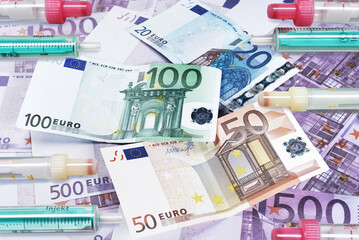 Syringes without needles over Euro Banknotes, vaccination budget