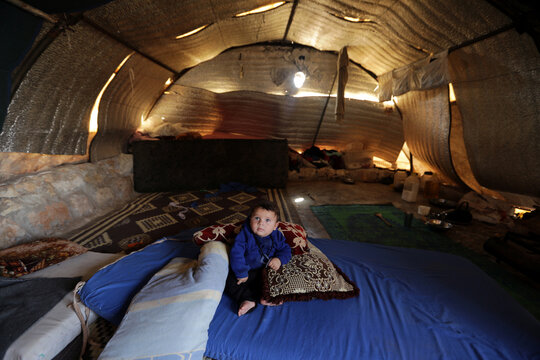 Abdul Rahman al-Fares, a 4-month-old Syrian displaced baby from south Idlib countryside, poses for a picture in a tent at Atmeh camp