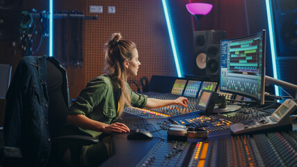 Beautiful Female Audio Engineer Working in Music Recording Studio, Uses Mixing Board and Software to Create Modern Sound. Creative Girl Artist Musician Working on Control Desk to Produce New Song