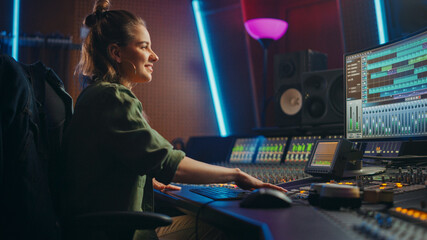 Beautiful, Stylish Female Audio Engineer and Producer Working in Music Recording Studio, Uses...