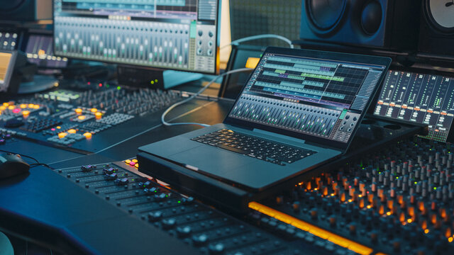 Modern Music Record Studio Control Desk with Laptop Screen Showing User Interface of Digital Audio Workstation Software. Equalizer, Mixer and Professional Equipment. Faders, Sliders. Record. Close-up