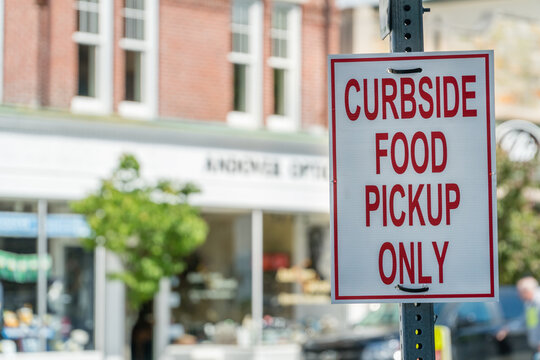 """Close-up of sign outside of restaurant stating """"Curbside Food Pickup Only"""" during phased reopening of businesses during the Covid-19 pandemic."""