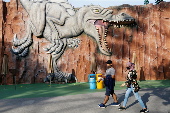 Visitors wearing protective masks walk past a wall depicting a dinosaur on the first day of reopening at the Ancol Dreamland: Dunia Fantasi amusement park amid the coronavirus disease (COVID-19) outbreak