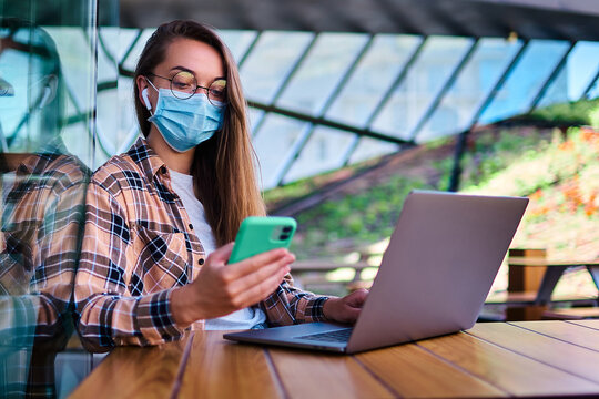 Casual woman freelancer in face mask, wireless headphones and eyeglasses using phone and laptop for remotely working online in cafe. Modern people with mobility lifestyle