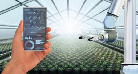 A farmer controls agricultural robot through a smartphone mobile application. Smart farming and...