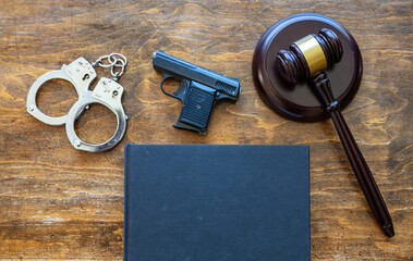 Law, crime, punishment concept. Judge gavel, handgun, handcuffs and a black blank legal book on wooden brown desk background, space.