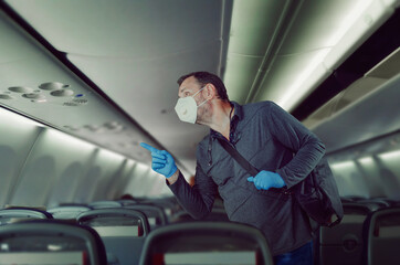 Middle-aged man in white face mask and blue rubber gloves is finding his seat on a plane