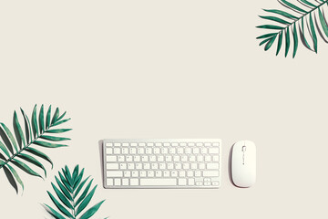 Computer keyboard and mouse with tropical leaves
