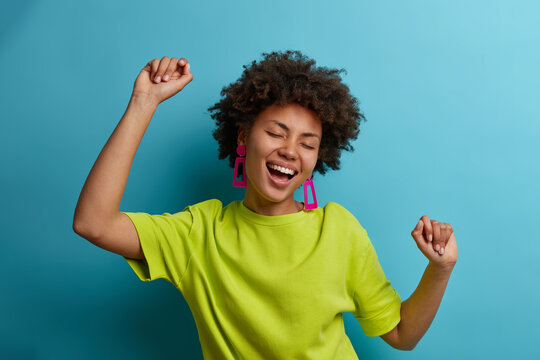I am winner! Ecstatic overjoyed African American woman dances carefree, celebrates victory and success, dressed in green casual t shirt, feels lively and energetic, isolated on blue background