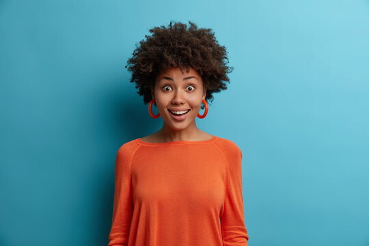 Portrait of happy surprised Afro American woman stands with amazed face expression, reacts crazy on awesome news, dressed in orange jumper, poses against blue background, looks with disbelief