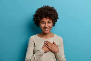 Kind positive African American woman expresses gratitude, has good feeling, presses hands to heart,...