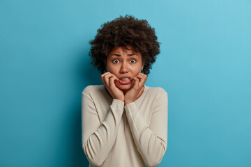 Portrait of puzzled nervous woman grabs face and looks anxiously at camera, trembles from fear,...