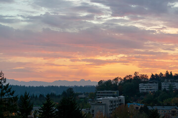 Colorful sky over Northwest Cascade Range during sunrise hours on Mercer Island in Washington state on an autumn day.