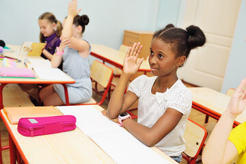 a small African-American schoolgirl stretches her hand up and smiles against the background of a classroom and a group of classmates. Back to school, knowledge day.