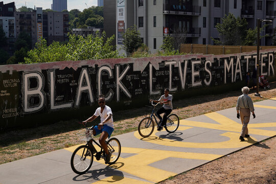 People pass a plywood wall with 'Black Lives Matter' and the names of police shooting victims on it, in Atlanta