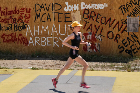 A woman jogs past a plywood wall with the names of Black shooting victims, including Ahmaud Arbery, who was shot while jogging, in Atlanta
