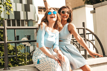 Two young beautiful smiling hipster girls in trendy summer clothes.Sexy carefree women posing on...