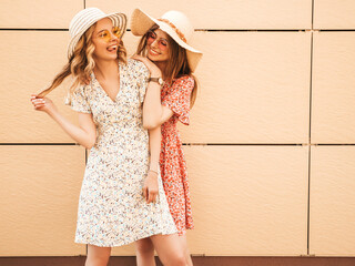 Two young beautiful smiling hipster girls in trendy summer sundress.Sexy carefree women posing near...