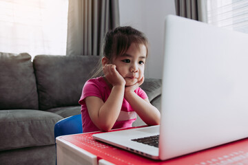 Asian children are interested in learning while teachers are teaching online via the internet...