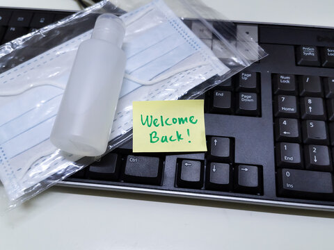 Welcome note with hand sanitizer and mask on work keyboard