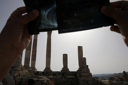 A man uses an X-ray film to observe a partial solar eclipse at the Amman Citadel, an ancient Roman landmark, in Amman