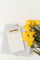 Beautiful modern office workspace with clipboard and stationery and tulip flowers. Flatlay, top...