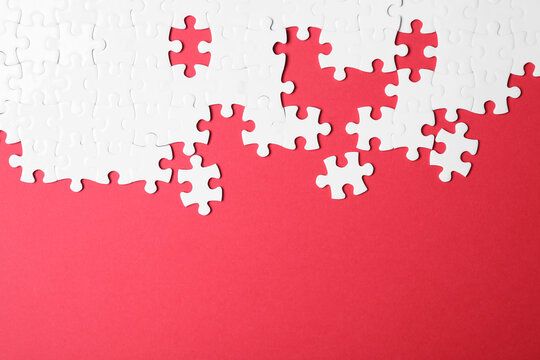 Blank white puzzle pieces on red background, flat lay. Space for text