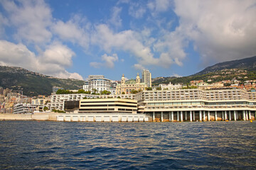 View from the Mediterranean sea of the Principality of Monaco, and Monte Carlo, with dense skyscrapers, the marina, palace & casino.