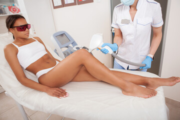 Full length shot of a gorgeous African woman getting laser hair removal on her legs at beauty clinic
