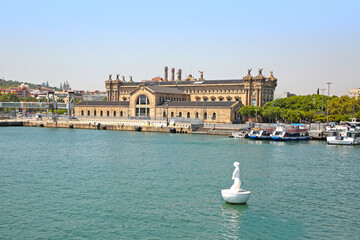 View across the harbour towards the city including the Columbus Monument, floating footballer and the old customs building at Port Vell, Barcelona, Spain.