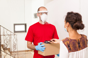 Delivery man wearing protection mask while woman paying package.
