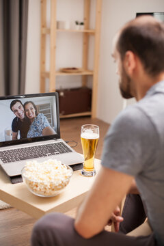 Man with a glass of beer on the table on video call with his friends during social distancing.