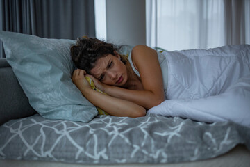 Lifestyle night portrait of young sad and stressed  woman lying on bed upset trying to sleep suffering insomnia and depression feeling anxiety crisis and sleeping disorder problem
