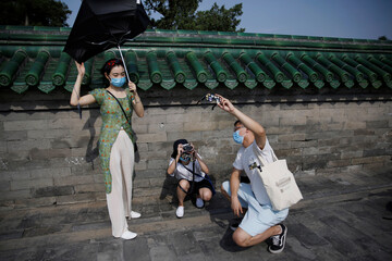 Woman takes photos of the partial solar eclipse as a man holds protective glasses at the Temple of Heaven park, following an outbreak of the coronavirus disease (COVID-19), in Beijing