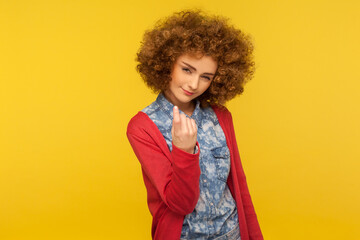 Come here, follow me! Portrait of pretty curly-haired woman looking playfully and calling with one finger, making beckoning gesture, inviting to come. indoor studio shot isolated on yellow background