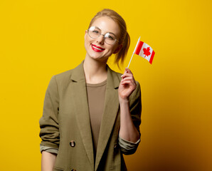 Style blonde woman in jacket with Canadian flag on yellow background