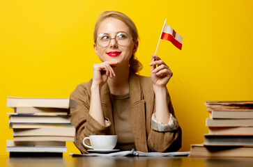 blonde woman with flag of Poland and books on yellow background