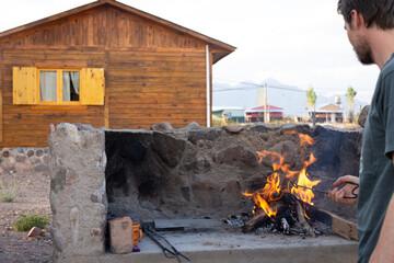 Jeune homme devant un barbecue et une cabane en bois